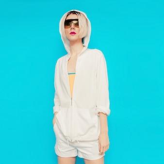 Modell in modischer weißer sportkleidung. kapuzenpullover & shorts