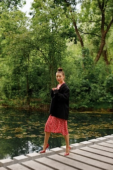Modell in stilvoller kleidung auf einem spaziergang im sommer im park. rote schuhe, rotes kleid, schwarze jacke. die lippen sind mit rotem lippenstift bemalt, die haare sind gesammelt.