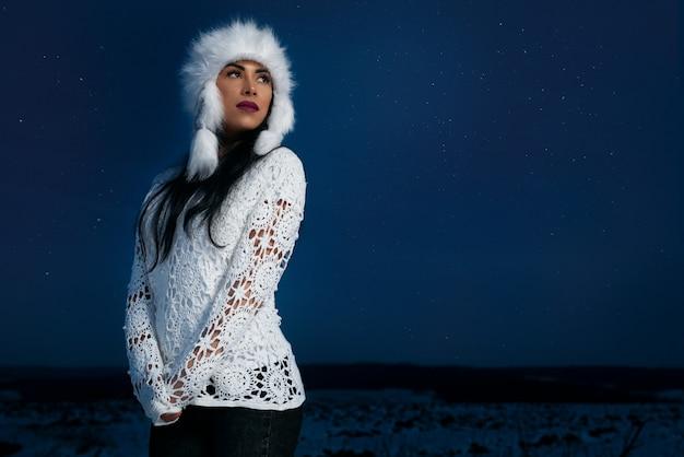 Modell in stilvoller warmer mütze, gestrickte bluse im freien in der nacht.