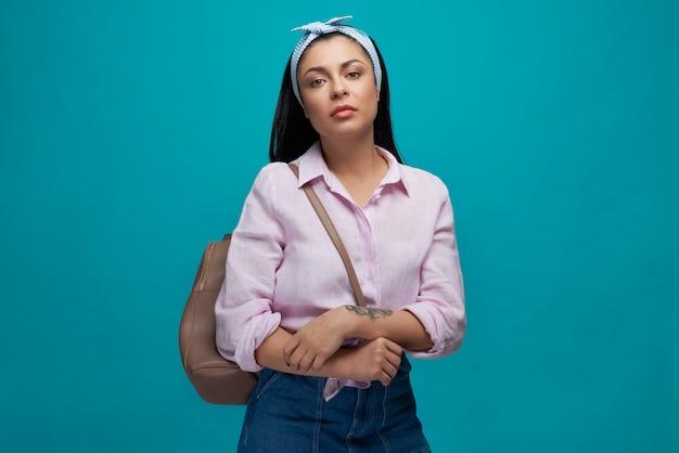 Modell in trendiger kleidung mit brauner tasche auf schulter.