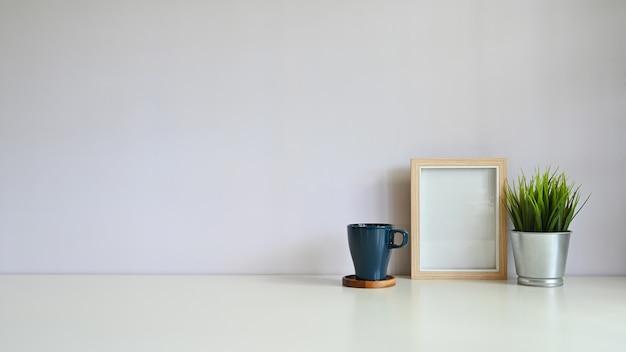 Modell-kopienraumschreibtischfotorahmen und -kaffee mit blumentopf auf weißem schreibtisch.