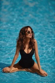 Modell mädchen mit einem sexy körper, großen brüsten und schlanker taille, in einem schwarzen badeanzug, der einen sommertag im schwimmbad draußen genießt