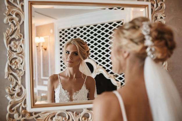 Modell mädchen mit platinblondem lockigem haar, das den spiegel im weinleseinnenraum betrachtet. junge blonde frau, die ihr gesicht durch den spiegel betrachtet. morgenvorbereitung der jungen braut