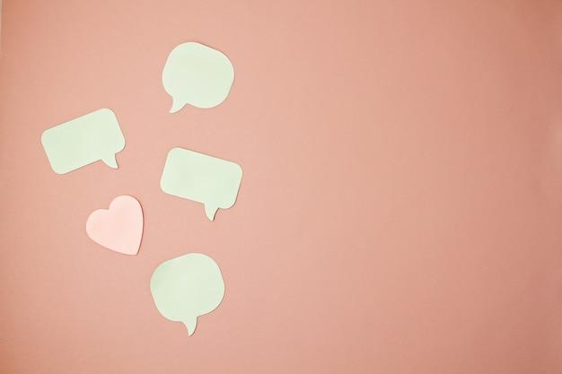 Modell mit aufkleberanmerkungen in den formen von spracheblasen und von herzen mit kopienraum