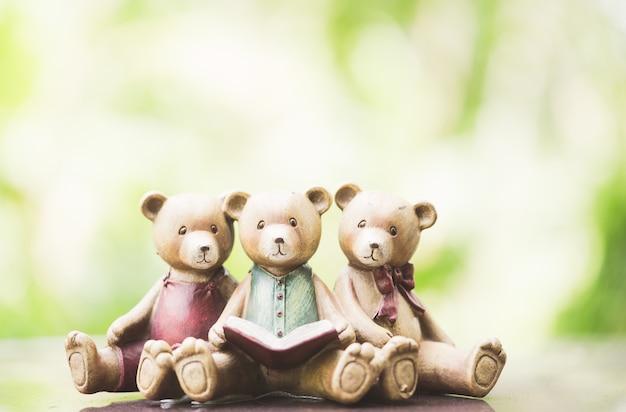 Modell mit drei teddybären, das ein buch auf grünem hintergrund liest.