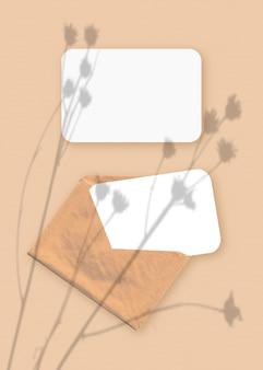 Modell mit einer überlagerung von pflanzenschatten auf einem umschlag mit zwei blättern strukturiertem weißem papier auf einem beigen tischhintergrund. vertikale ausrichtung.