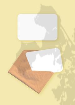 Modell mit einer überlagerung von pflanzenschatten auf einem umschlag mit zwei blättern strukturiertem weißem papier auf einem gelben tischhintergrund. vertikale ausrichtung.