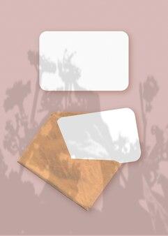 Modell mit einer überlagerung von pflanzenschatten auf einem umschlag mit zwei blättern strukturiertem weißem papier auf einem rosafarbenen tischhintergrund. vertikale ausrichtung.