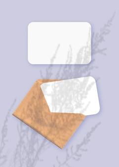 Modell mit einer überlagerung von pflanzenschatten auf umschlag mit zwei blättern strukturiertem weißem papier auf violettem tischhintergrund. vertikale ausrichtung.
