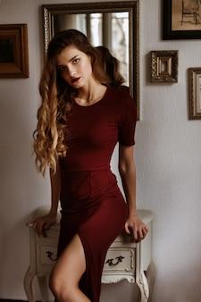 Modell mit langen haaren in einem burgunderfarbenen kleid. pariser stil. sexy schlankes mädchen