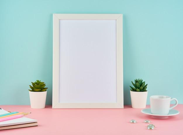 Modell mit leerem weißem rahmen, betriebskaktus, tasse kaffee oder tee auf rosa tabelle gegen blaue wand