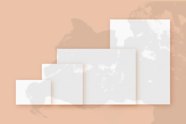 Modell mit pflanzenschatten, die auf mehreren horizontalen und vertikalen blättern aus strukturiertem weißem papier auf einem beigen tischhintergrund überlagert sind.