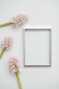Modell mit rosa blumen und leerem fotorahmen mit kopierraum.