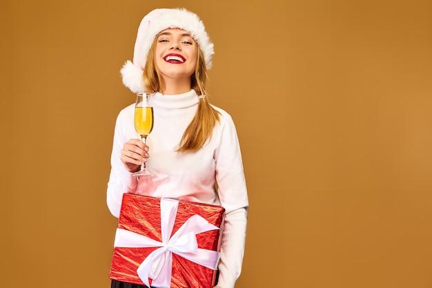 Modell mit weihnachtsmütze und großer geschenkbox, die champagner auf goldener wand trinkt