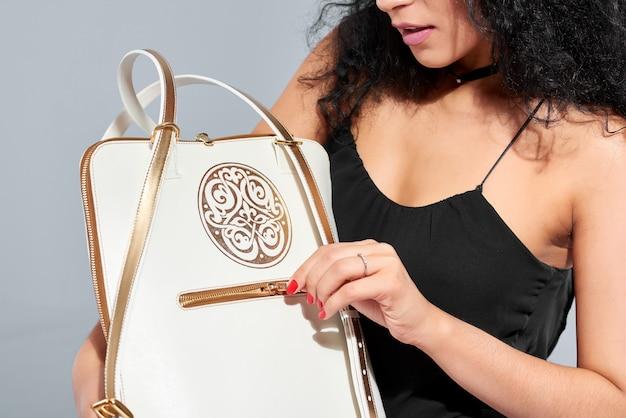 Modell mit weißer tasche mit goldenem muster, griffen und kleinem reißverschluss.