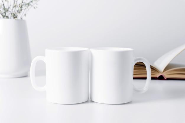 Modell mit zwei tassen mit buch und blumen in einer vase auf einem weißen tisch