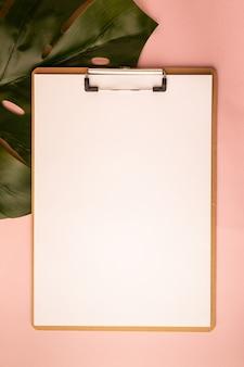 Modell mit zwischenablage und monstera-blatt auf rosa hintergrund. flache lage, ansicht von oben, kopienraum.