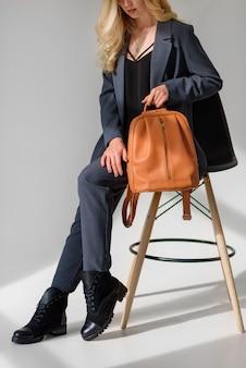 Modell posiert sitzend auf einem stuhl