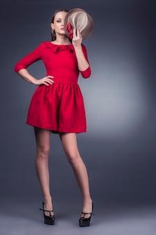 Modell schöne frauen in modischen kleidern und accessoires erschossen isoliert auf einem schwarzen hintergrund