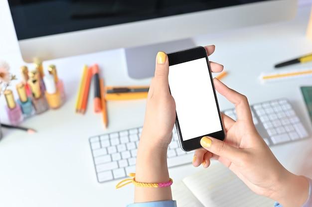 Modell smartphone auf frauenhänden mit auf büroarbeitsplatz.