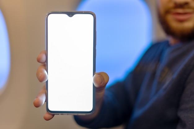 Modell smartphone flugzeug. junger attraktiver kaukasischer mann, der smartphone des leeren bildschirms in den händen im flugzeug hält