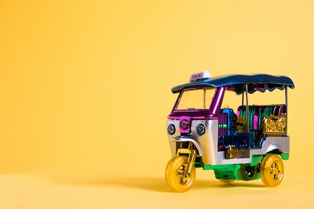 Modell toy tuk tuk isoliert auf gelber wand. traditionelles thailändisches taxi in bangkok thailand. souvenir