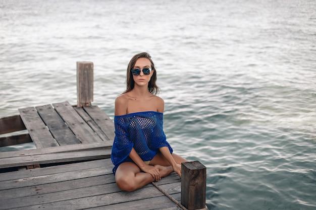 Modell trägt blaue kleidung und sonnenbrille, die auf einer holzbrücke vor dem hintergrund des kristallklaren wassers sitzen und posieren.