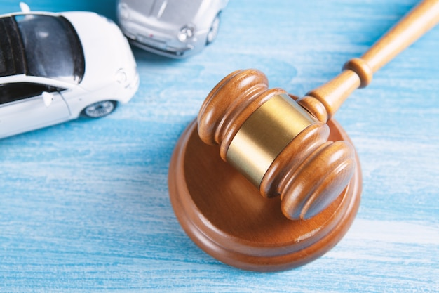 Modell von auto und hammer. unfallklage oder versicherung, gerichtsverfahren.