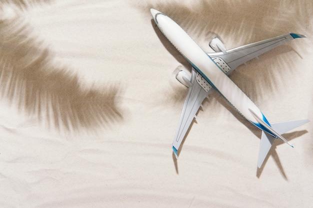 Modell von flugzeug, flugzeug und palmblättern schatten auf goldsandhintergrund. flaches lay-design. reise, urlaubskonzept
