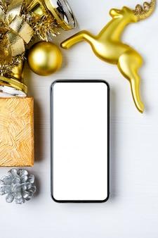 Modell von smartphone mit goldenen weihnachtsdekorationen