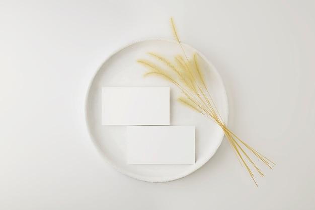 Modell von visitenkarten auf einem weißen weinlese-teller mit trockener pflanze