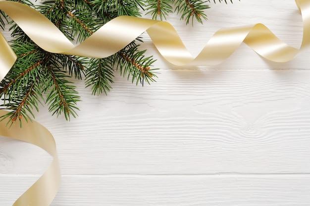 Modell-weihnachtsbaum und goldband, flatlay auf einem weißen hölzernen