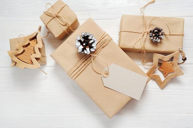 Modell-weihnachtsgeschenk-geschenkbox und -tag auf hölzernem