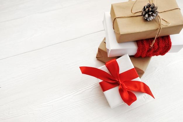 Modell-weihnachtsgeschenkbox auf hölzernem hintergrund mit schneeflocken