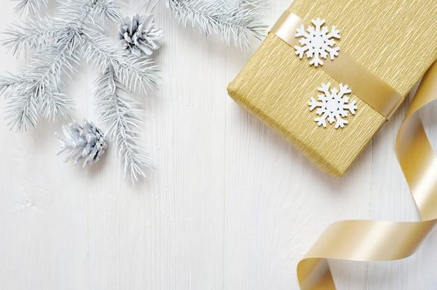 Modell-weihnachtsgeschenkgoldbogen und baumkegel, flatlay auf einem weißen hölzernen