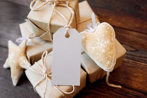 Modell-weihnachtskraftpapier-geschenkboxen mit tag auf hölzernem hintergrund. weihnachtsgrußkarte