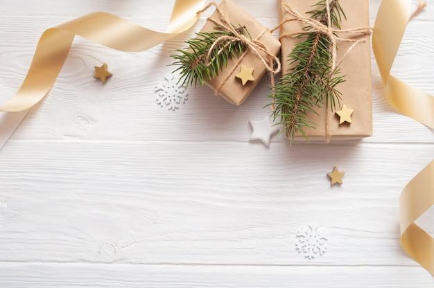Modell-weihnachtskraftpapier-geschenkboxen mit tag auf holz