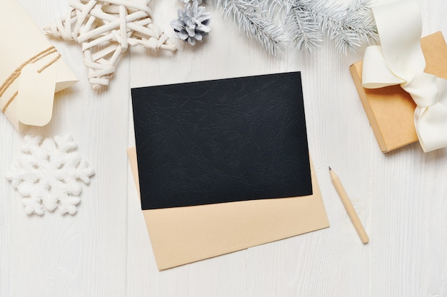 Modell-weihnachtsschwarz-grußkartenbuchstabe im umschlag mit weißem baum