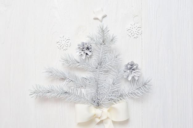 Modell-weihnachtsweißer baum und -kegel. flatlay auf einem weißen holz