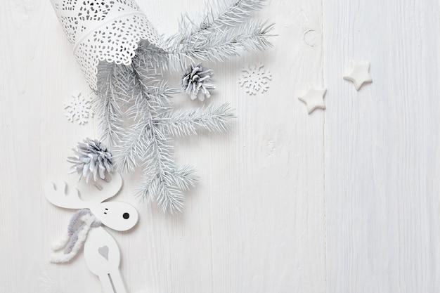 Modell-weihnachtsweißer baum und kegel, rotwild. flatlay auf einem weißen hölzernen hintergrund