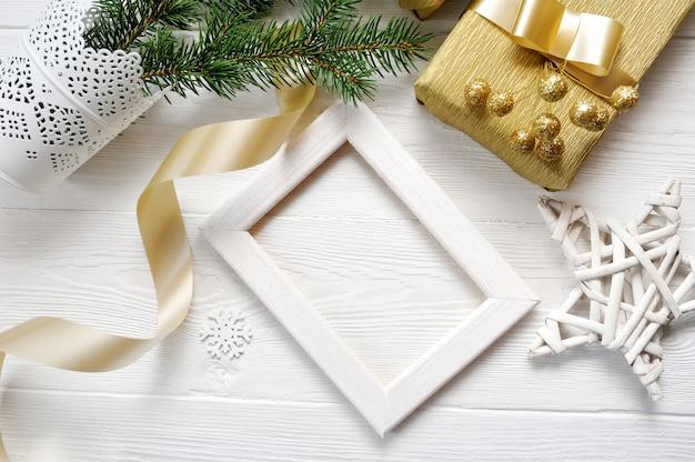 Modell-weihnachtsweißer rahmen mit baum und goldenem band und ein geschenk
