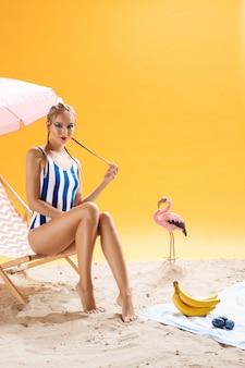 Modell wirft mit hand auf gesicht, das auf sommerdekor sitzt