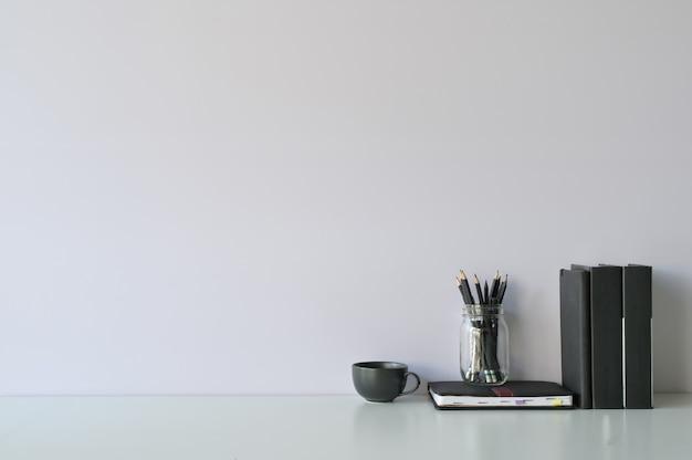 Modellarbeitsplatzschreibtisch und kopienraumbücher, -kaffee und -bleistift auf weißem schreibtisch.