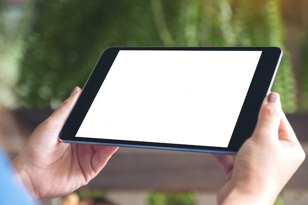 Modellbild der frau, die schwarzen tablett-pc mit weißem leerem desktop-bildschirm hält