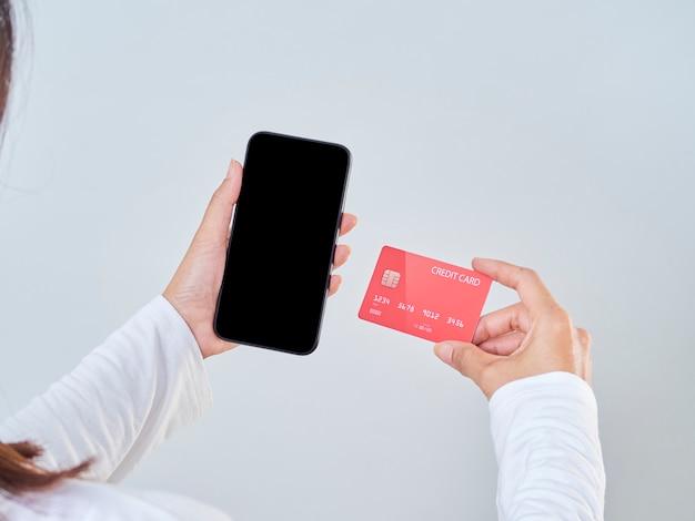 Modellbild der frauenhand, die handy, leeren bildschirm und kreditkarte auf grauem hintergrund hält