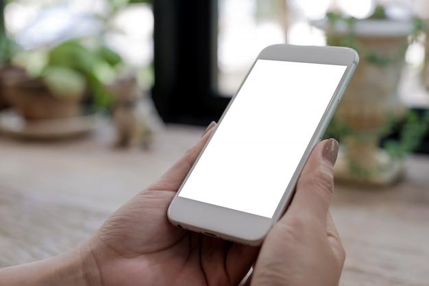 Modellbild der hände der frau, die handy mit leerem weißen bildschirm auf holztisch im weinlesecafé halten