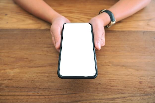 Modellbild der hände der frau, die schwarzes handy mit leerem weißen bildschirm auf holztisch halten
