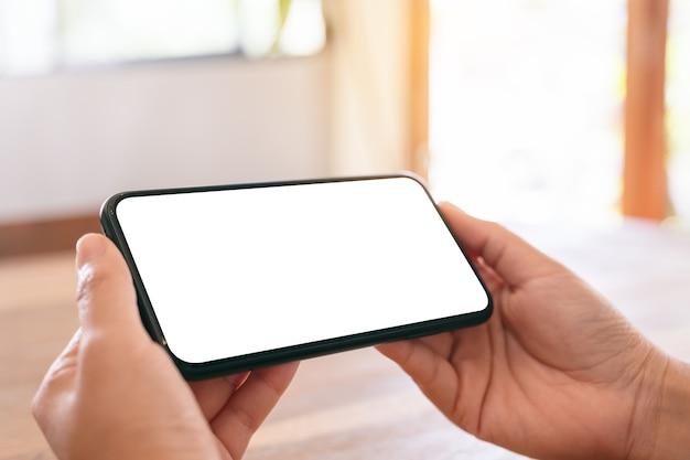Modellbild der hände der frau, die schwarzes handy mit leerem weißen bildschirm horizontal auf holztisch halten