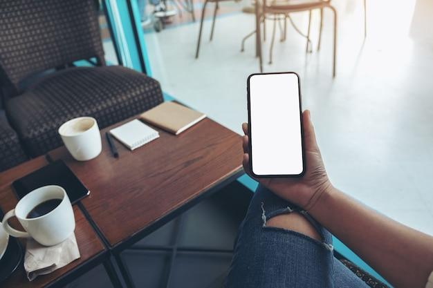 Modellbild der hände der frau, die schwarzes handy mit leerem weißen bildschirm im café halten