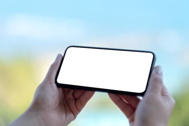 Modellbild der hände der frau, die schwarzes handy mit leerem weißen bildschirm mit unscharfem naturhintergrund halten